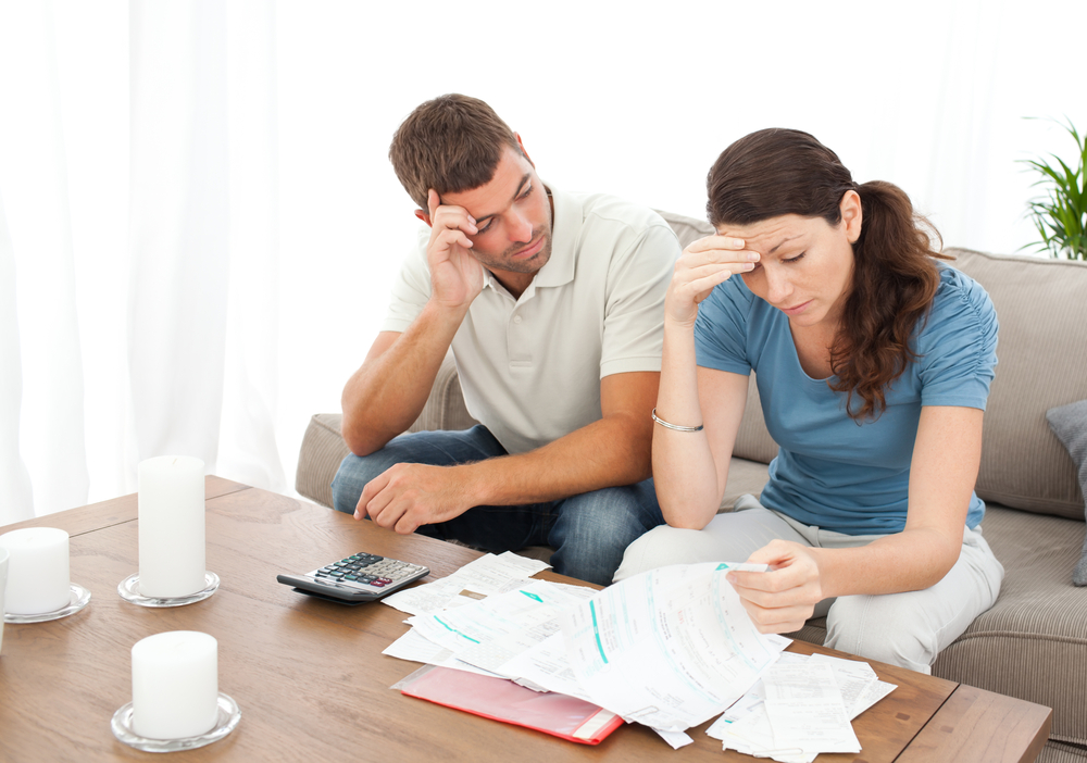 Worried couple doing their accounts in the living room at home-1
